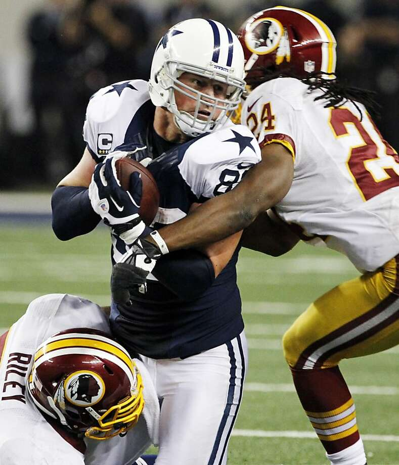 Dallas Cowboys tight end Jason Witten (82) is stopped by Washington Redskins' Perry Riley, bottom, and DeJon Gomes (24) after grabbing a pass late in the second half of an NFL football game, Thursday, Nov. 22, 2012, in Arlington, Texas. The Redskins won 38-31. (AP Photo/Tim Sharp) Photo: Tim Sharp, Associated Press