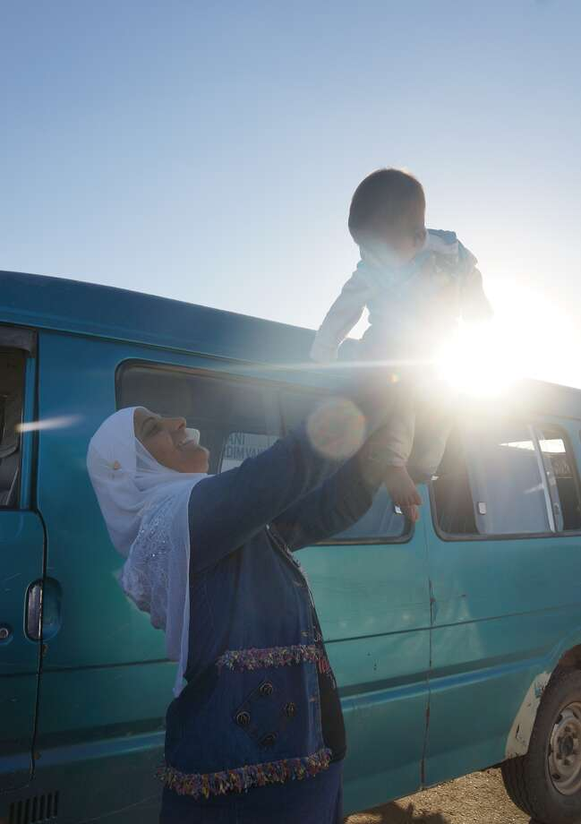 Photo courtesy Matthew Schrier A Syrian refugee woman lifts a child near a refugee camp in Kilis, Turkey.