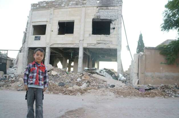 Photo courtesy Matthew Schrier A boy stands before a bombed-out building and rubble in Azaz, Syria, a rebel-held town decimated by Syrian Air Force bombings.