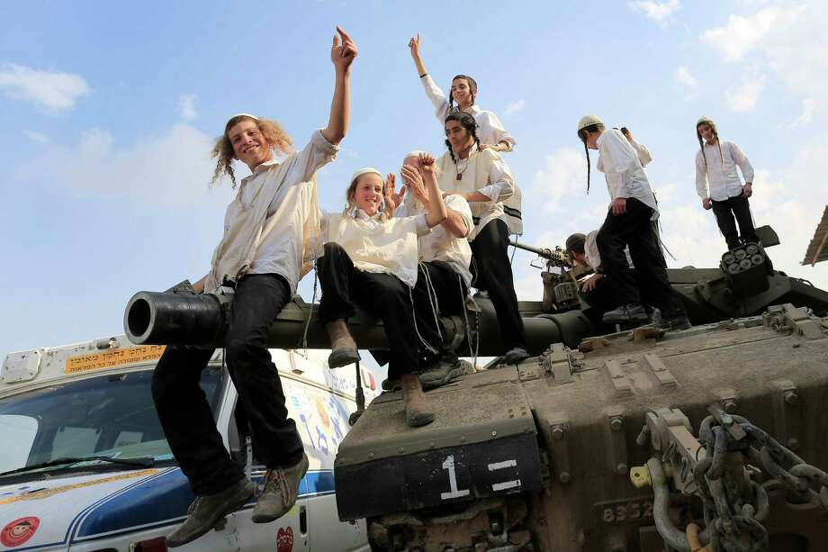Ultra-Orthodox Jews of the Bratslav Hasidic sect, that gathered to show support for the forces, dance as they celebrate atop of a tank in southern Israel, close to the Israel Gaza Strip Border, Thursday, Nov. 22, 2012. A cease-fire agreement between Israel and the Gaza Strip's Hamas rulers took effect Wednesday night, bringing an end to eight days of the fiercest fighting in years and possibly signaling a new era of relations between the bitter enemies. (AP Photo/Tsafrir Abayov) Photo: Tsafrir Abayov