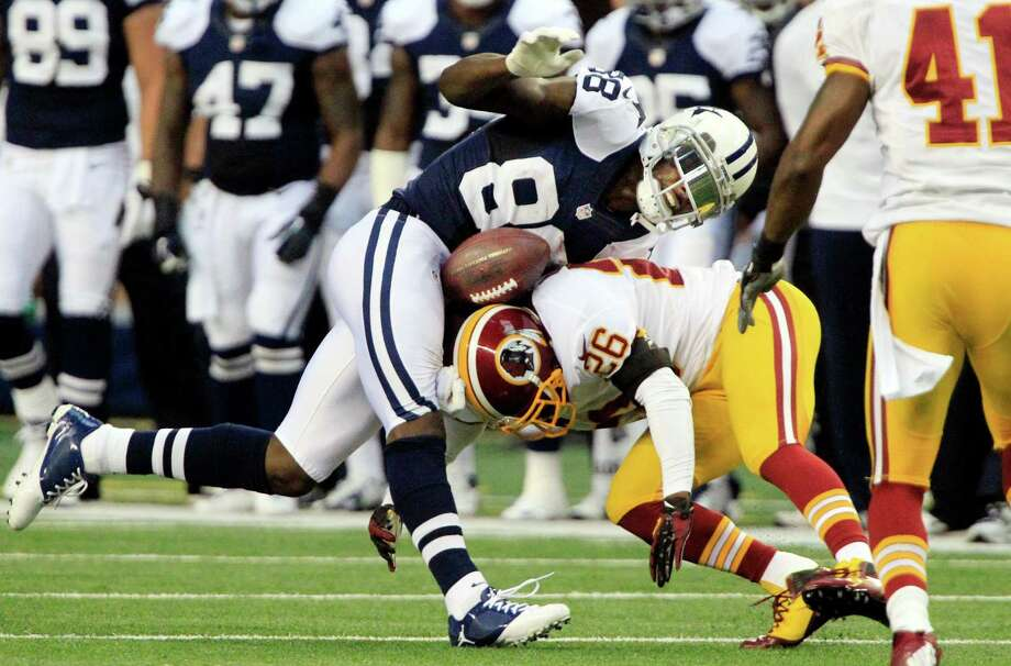 Redskins cornerback Josh Wilson (26) uses his head to force a fumble by Cowboys wide receiver Dez Bryant at Texas Stadium on Thursday. Washington recovered the ball and soon scored a touchdown as part of a 28-point, second-quarter explosion. Photo: John Rhodes / Fort Worth Star-Telegram