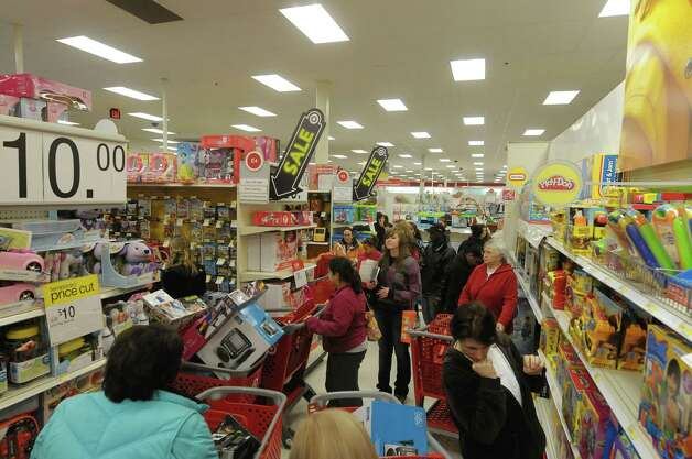 Shoppers look over items in the toy department at the Target store on Thursday evening, Nov. 22, 2012 in Colonie, NY.  The store opened at 9pm on Thursday evening, giving shoppers an early start on black friday shopping.  (Paul Buckowski / Times Union) Photo: Paul Buckowski  / 00020212A