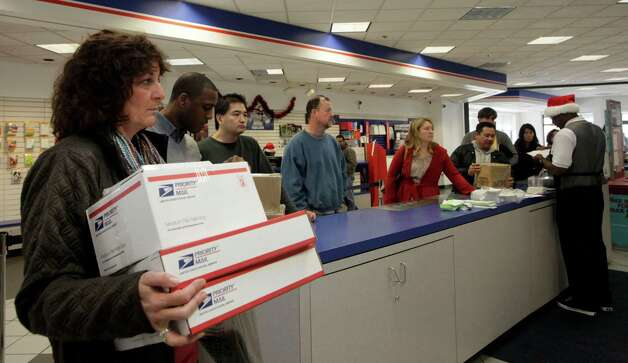 FILE - This Dec. 19, 2011 file photo shows people in line at the U.S. Postal Service Airport station in Los Angeles. Emboldened by rapid growth in e-commerce shipping, the cash-strapped U.S. Postal Service is moving aggressively this holiday season to start a premium service for the Internet shopper seeking the instant gratification of a store purchase: same-day package delivery. (AP Photo/Nick Ut, File) Photo: Nick Ut