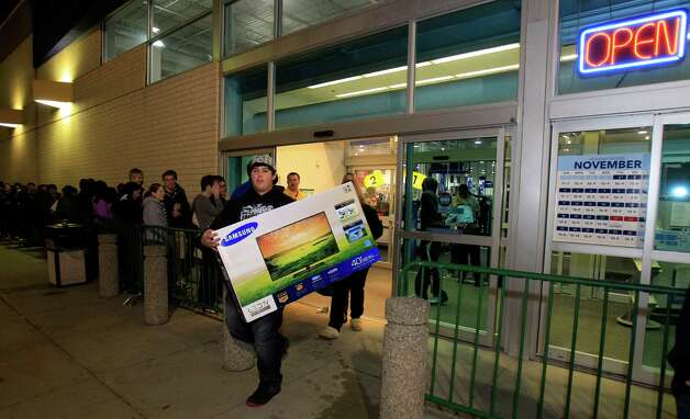 Christian Adorno, 13, walks out of a Best Buy with a 40-inch television Friday, Nov. 23, 2012, in Mayfield Heights, Ohio. The store opened at 12 a.m. on Friday. Photo: Tony Dejak