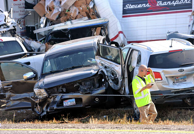 An emergency worker walks past a pile of cars from the accident on Interstate in Southeast Texas Thursday Nov. 22, 2012.  The Texas Department of Public Safety says at least 35 people have been injured in a more than 50-vehicle pileup.    (AP Photo/The Beaumont Enterprise, Guiseppe Barranco) Photo: Guiseppe Barranco