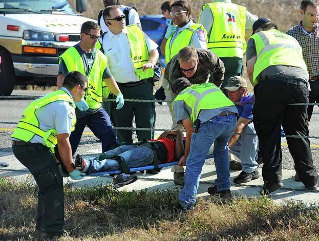 Emergency workers carry a victim across the Interstate 10 median after a massive auto accidentin Southeast Texas Thursday Nov. 22, 2012.  The Texas Department of Public Safety says at least 35 people have been injured in a more than 50-vehicle pileup.    (AP Photo/The Beaumont Enterprise, Guiseppe Barranco)MANDATORY CREDIT Photo: Guiseppe Barranco