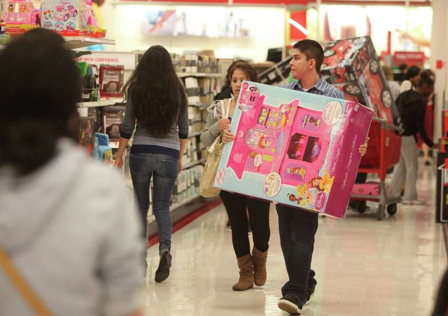 Werner Orellana carries a Christmas gift toy for his daughter while shopping the Black Friday deals at Target on Thursday, Nov. 22, 2012, in Houston. Photo: Mayra Beltran, Houston Chronicle / © 2012 Houston Chronicle
