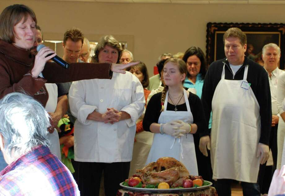 The Rev. Alison Patton, minister of Saugatuck Congregational Church, offers a blessing over the first bird Thursday at the church's annual community Thanksgiving feast.  Westport CT 11/22/12 Photo: Jarret Liotta / Westport News contributed