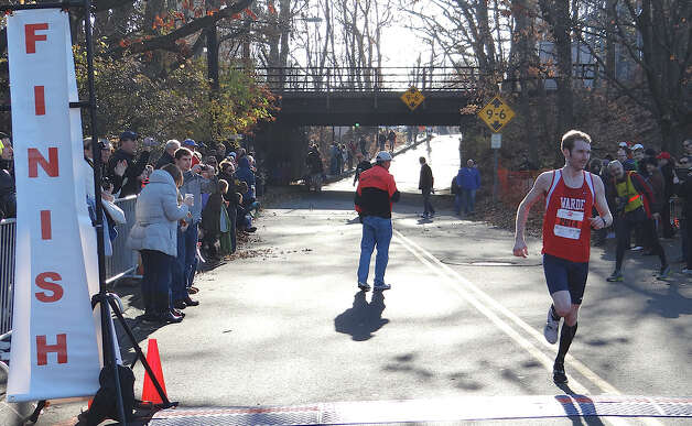 Matthew Kane, 22, of Fairfield, crosses the finish line Thursday to win the 35th annual Pequot Turkey Trot in a time of 25:23.  Fairfield CT 11/22/12 Photo: Mike Lauterborn / Fairfield Citizen contributed