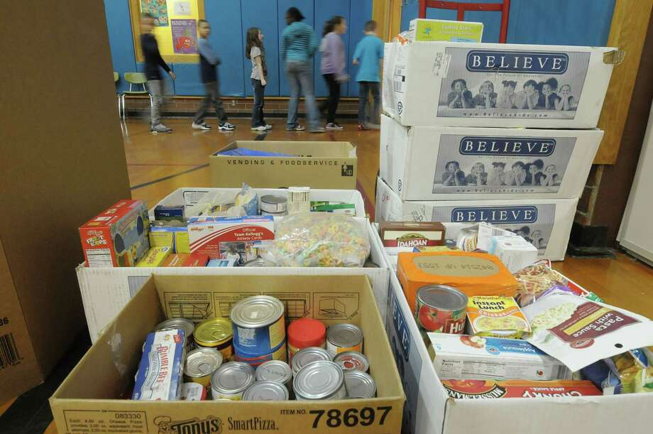 Boxes of donated food items are seen stacked as students exit the gym following an assembly at Rensselaer Park Elementary School on Monday, Nov. 19, 2012 in Lansingburgh, NY.  The assembly was the culmination of a service learning project where the students at each grade level donated food items and other items to be given to a local organization that helps the needy.  The third grade collected items for the Rensselaer County Office of the Aging, the fourth grade collected items for St. Paul's Center and the fifth grade collected items for The Unity House of Troy.  All total the students collected and donated over 800 items for the organizations.    (Paul Buckowski / Times Union) Photo: Paul Buckowski