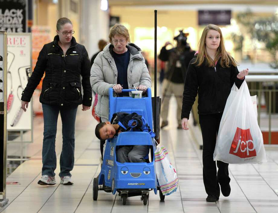 Krystal Phillips, left walks with her mom, Teary Ray, center and sister Megan Ray, right while wheeling a very tired Rahshawn Phillips, 3, Krystal's son at Crossgates Mall in Guilderland, N.Y. on Black Friday Nov 23, 2012.      (Skip Dickstein/Times Union) Photo: Skip Dickstein, Albany Times Union / 00020194A