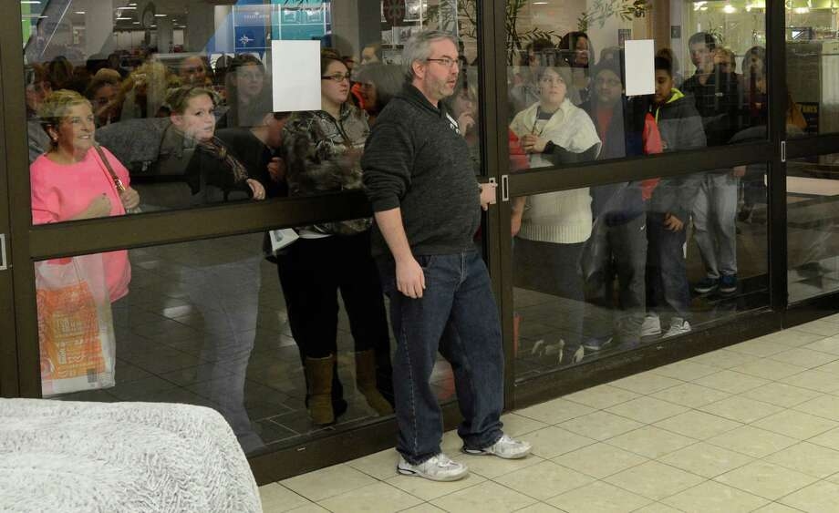 Shoppers wait patiently for the 6:00 am opening as supervisor Kevin Jojo holds the key to the door of J. C. Penney at Crossgates Mall in Guilderland, N.Y. on Black Friday Nov 23, 2012.      (Skip Dickstein/Times Union) Photo: Skip Dickstein, Albany Times Union / 00020194A