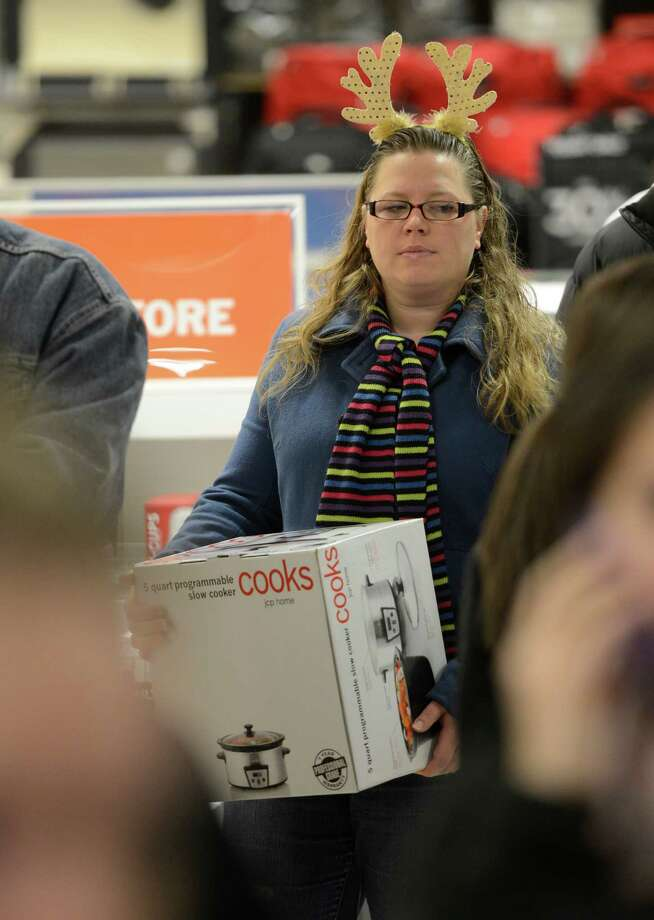 Heather Dwyer of New Baltimore wears her holiday antlers and holds a gift while waiting in line to cash out at J. C. Penney at Crossgates Mall in Guilderland, N.Y. on Black Friday Nov 23, 2012.      (Skip Dickstein/Times Union) Photo: Skip Dickstein, Albany Times Union / 00020194A