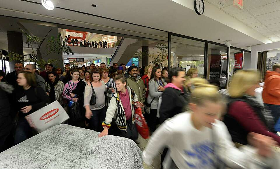 Shoppers rush through the door at 6 a.m. on Black Friday at JCPenney at Crossgates Mall in Guilderla