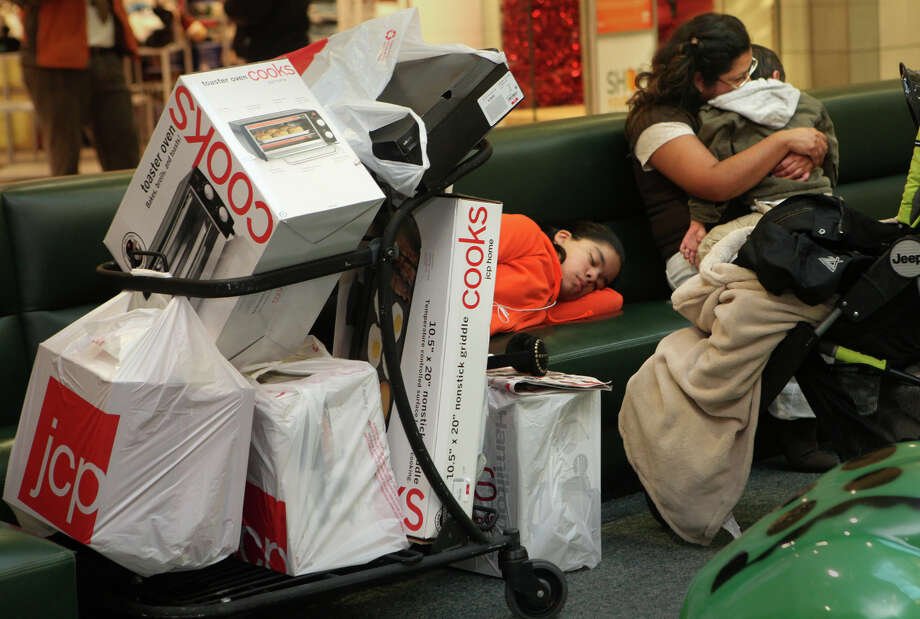 Rosey Flores, of West Haven, comforts her son, Pablo, 3, as her daughter Allison, 11, sleeps, after a full night of shopping at the Westfield CT Post Mall in Milford, Conn. on Friday, November 23, 2012. Photo: BK Angeletti, B.K. Angeletti / Connecticut Post freelance B.K. Angeletti