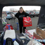 """Nancy Appleton, of West Haven, completes and loads her holiday shopping into her trunk at Walmart in Milford, Conn. on Friday, November 23, 2012.  """"I'm done, I'm done!"""" exclaimed Appleton as she loaded her trunk."""