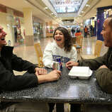 Friends, from left, Paul Stumbo, Jessica O'Connor, and Christian Sobin, drink Red Bulls after shopping at the Westfield Connecticut Post Mall in Milford, Conn. on Friday, November 23, 2012.