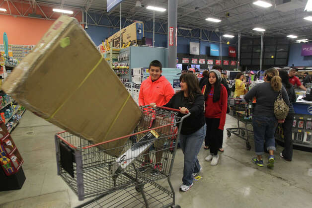 Shopper Eva Avalos pushes a shopping cart out of the electronics area of the H-E-B plus! store at Blanco and Loop 1604 Black Friday November 23, 2012. Photo: JOHN DAVENPORT, San Antonio Express-News / ©San Antonio Express-News/Photo Can Be Sold to the Public