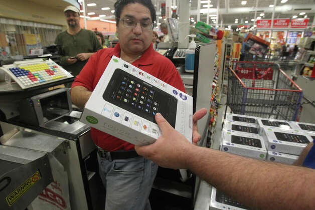 H-E-B employee Alex Perez gets ready to sell an electronic tablet shortly after 6:00 a.m. Black Friday November 23, 2012 at the H-E-B plus! on Loop 1604 at Blanco road. Photo: JOHN DAVENPORT, San Antonio Express-News / ©San Antonio Express-News/Photo Can Be Sold to the Public