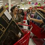 """Bianca Castillo, left,and her cousin Gabriella Alejo, right, smile after getting  32"""" TVs at a Target in Austin, Texas, shortly after it opened at 9 p.m. on Thursday Nov. 22, 2012, for early Black Friday sales."""