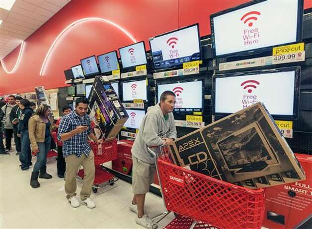 Shoppers use their smart phone with the Free Wi-Fi service, while waiting in line to pay for electronics at the Target store in Burbank, Calif., on Thursday, Nov. 22, 2012. While stores typically open in the wee hours of the morning on the day after Thanksgiving known as Black Friday, openings have crept earlier and earlier over the past few years. Now, stores from Wal-Mart to Toys R Us are opening their doors on Thanksgiving evening, hoping Americans will be willing to shop soon after they finish their pumpkin pie. Photo: Damian Dovarganes, AP / AP2012