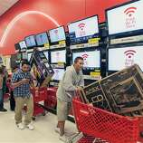 Shoppers use their smart phone with the Free Wi-Fi service, while waiting in line to pay for electronics at the Target store in Burbank, Calif., on Thursday, Nov. 22, 2012. While stores typically open in the wee hours of the morning on the day after Thanksgiving known as Black Friday, openings have crept earlier and earlier over the past few years. Now, stores from Wal-Mart to Toys R Us are opening their doors on Thanksgiving evening, hoping Americans will be willing to shop soon after they finish their pumpkin pie.
