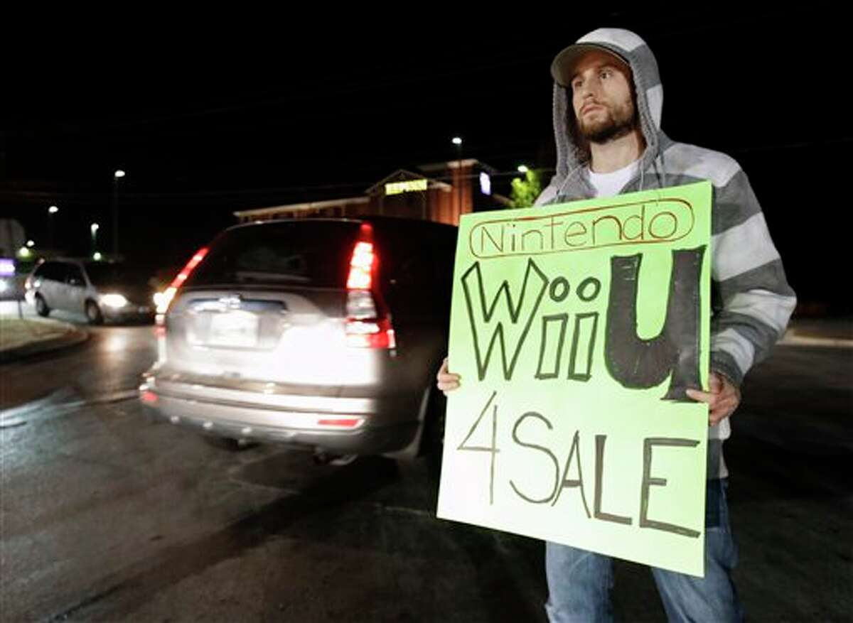Allan Abbott advertises Nintendo Wii U video games he is selling as shoppers drive by outside a shopping complex on Friday, Nov. 23, 2012, in Franklin, Tenn. Abbott said he was able to buy several of the popular games and is selling them below what they can be found for online. Black Friday got off to its earliest start ever as some of the nation's stores opened Thursday night.