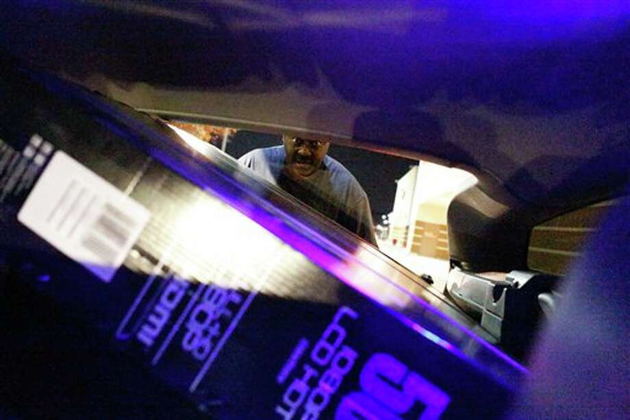 "Byron Hall loads a 50"" LCD television into his car during the Black Friday specials at the Super Target on Skillman Street in Dallas on Thursday Nov. 22, 2012. Photo: Stan Olszewski, AP / Dallas Morning News"