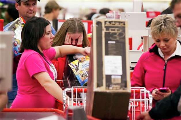 Amanda Benton, center, of Texarkana, Ark., gets light headed as she waits in line at a Target store in Texarkana, Texas with Franziska Santifer, left, also of Texarkana, Ark., during a Black Friday sale Thursday night Nov. 22, 2012. Over 1,000 customers waited in line for the store opening at 9 p.m. Photo: Adam Sacasa, AP / Texarkana Gazette