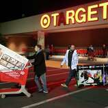 """Trevor Anderson, Mike Van Lone, and Zack McElwain (left to right) walk out with the televisions they purchased at Target, which opened at 9 p.m. as shoppers took advantage of the sales and deals in the earlier shopping period for the typical """"Black Friday"""" event on Thursday evening, Nov. 22, 2012 in Chico, Calif."""