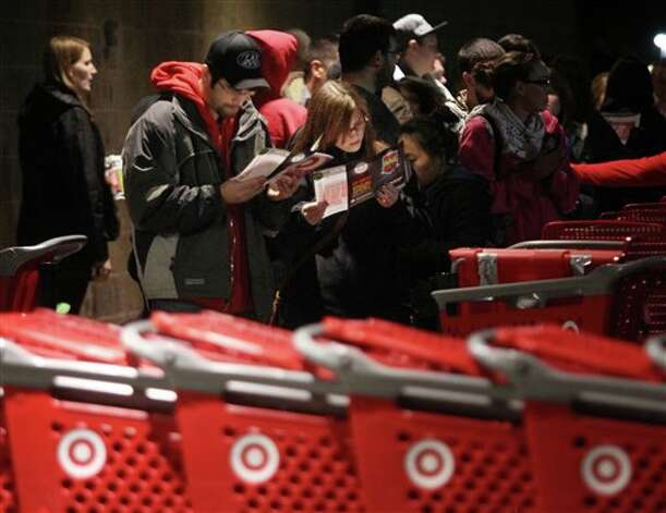"Matt Alcover (left) and Rebecca Hoyland (right) take a look at a map of Target as they wait in line before its opening at 9 p.m. as shoppers took advantage of the sales and deals in the earlier shopping period for the typical ""Black Friday"" event on Thursday evening, Nov. 22, 2012 in Chico, Calif. Photo: Jason Halley, AP / MediaNews Group"