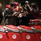 """Matt Alcover (left) and Rebecca Hoyland (right) take a look at a map of Target as they wait in line before its opening at 9 p.m. as shoppers took advantage of the sales and deals in the earlier shopping period for the typical """"Black Friday"""" event on Thursday evening, Nov. 22, 2012 in Chico, Calif."""