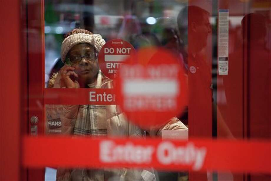One of the first in line, a woman talks on her cellphone next to the entrance of Target just minutes before the start of their Black Friday sales event in Flint, Mich. on Thursday, Nov. 22, 2012. Photo: Griffin Moores | MLive.com, AP / Flint Journal