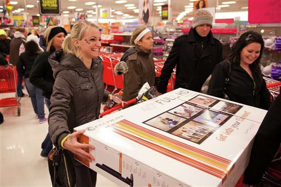 A joyful shopper laughs as she attempts to load a 40-inch TV into her cart at Target during their Black Friday sales event in Flint, Mich. on Thursday, Nov. 22, 2012. Photo: Griffin Moores | MLive.com, AP / Flint Journal