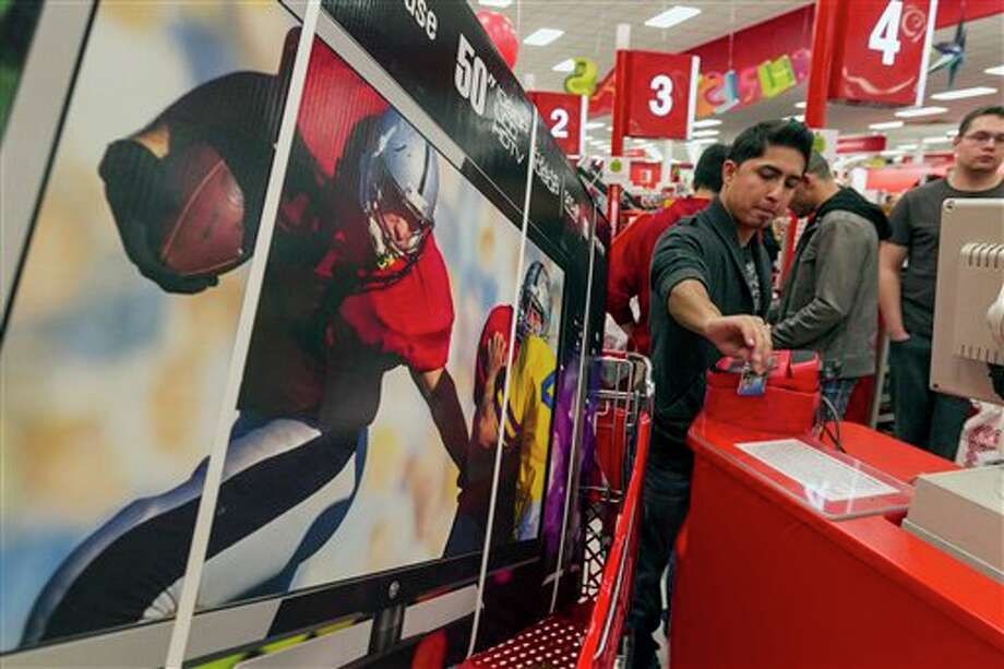 Consumer Ash Gan, 19, swipes his credit card to par for a television doorbuster deal at Target store in Burbank, Calif., on Thursday, Nov. 22, 2012. While stores typically open in the wee hours of the morning on the day after Thanksgiving known as Black Friday, openings have crept earlier and earlier over the past few years. Now, stores from Wal-Mart to Toys R Us are opening their doors on Thanksgiving evening, hoping Americans will be willing to shop soon after they finish their pumpkin pie. Photo: Damian Dovarganes, AP / AP2012