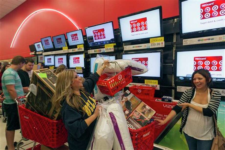 Shopper Roxanna Garcia, middle, waits in line to pay for  her over a $1000.00 gifts at the Target store in Burbank, Calif., on Thursday, Nov. 22, 2012. While stores typically open in the wee hours of the morning on the day after Thanksgiving known as Black Friday, openings have crept earlier and earlier over the past few years. Now, stores from Wal-Mart to Toys R Us are opening their doors on Thanksgiving evening, hoping Americans will be willing to shop soon after they finish their pumpkin pie. Photo: Damian Dovarganes, AP / AP2012