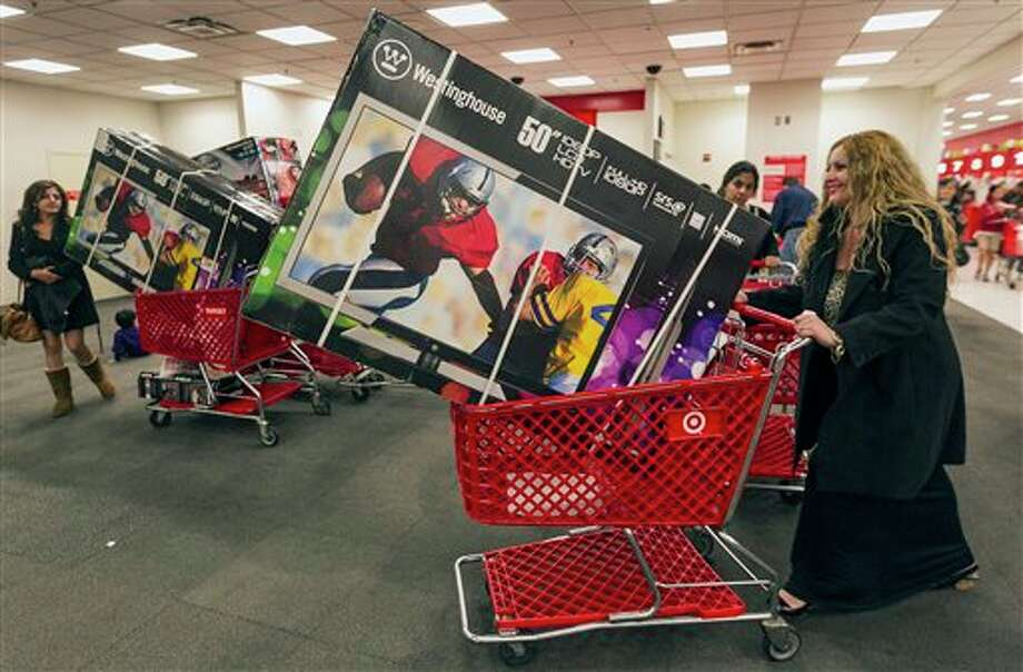 Shopper Lisa Camberos, right, gets a television doorbuster deal at the Target store in Burbank, Calif., on Thursday, Nov. 22, 2012. While stores typically open in the wee hours of the morning on the day after Thanksgiving known as Black Friday, openings have crept earlier and earlier over the past few years. Now, stores from Wal-Mart to Toys R Us are opening their doors on Thanksgiving evening, hoping Americans will be willing to shop soon after they finish their pumpkin pie. Photo: Damian Dovarganes, AP / AP2012