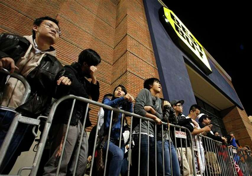 Shoppers stand in line outside a Best Buy department store waiting for the store's opening at midnig