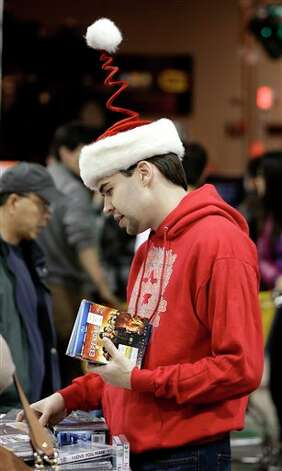 Clint Fletcher shops for movies at a Best Buy store on Friday, Nov. 23, 2012, in Franklin, Tenn., after the store opened at midnight.  Black Friday got off to its earliest start ever as some of the nation's stores opened Thursday night, beating the traditional Friday opening. Photo: Mark Humphrey, AP / AP2012