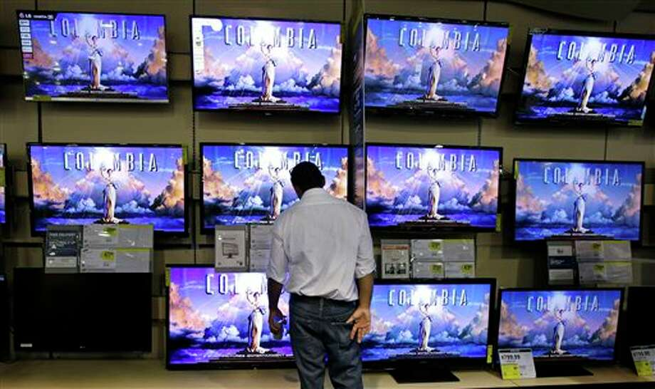 A shopper looks at televisions at a Best Buy store on Friday, Nov. 23, 2012, in Franklin, Tenn., after the store opened at midnight.  Black Friday got off to its earliest start ever as some of the nation's stores opened Thursday night, beating the traditional Friday opening. Photo: Mark Humphrey, AP / AP2012