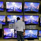 A shopper looks at televisions at a Best Buy store on Friday, Nov. 23, 2012, in Franklin, Tenn., after the store opened at midnight.  Black Friday got off to its earliest start ever as some of the nation's stores opened Thursday night, beating the traditional Friday opening.