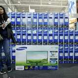 A customer who declined to be identified waits by a television she was purchasing at a Best Buy store, Friday Nov 23, 2012, in Northeast Philadelphia.