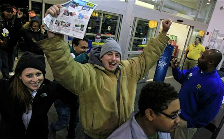 Ray Schwarz, 28, celebrates after waiting 24-hours to enter Best Buy Friday, Nov. 23, 2012, in Mayfield Heights, Ohio. The store opened at 12 a.m. on Friday. Schwarz is buying three televisions, a sound system and video games. Photo: Tony Dejak, AP / AP2012