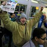 Ray Schwarz, 28, celebrates after waiting 24-hours to enter Best Buy Friday, Nov. 23, 2012, in Mayfield Heights, Ohio. The store opened at 12 a.m. on Friday. Schwarz is buying three televisions, a sound system and video games.