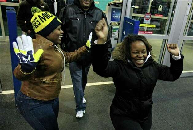 Teaje Price, left to right, 22, and Kristi Marshall, 42, celebrate as they enter a Best Buy Friday, Nov. 23, 2012, in Mayfield Heights, Ohio. The store opened at 12 a.m. on Friday. They are buying a television and a Blue-ray player. Photo: Tony Dejak, AP / AP2012