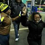 Teaje Price, left to right, 22, and Kristi Marshall, 42, celebrate as they enter a Best Buy Friday, Nov. 23, 2012, in Mayfield Heights, Ohio. The store opened at 12 a.m. on Friday. They are buying a television and a Blue-ray player.