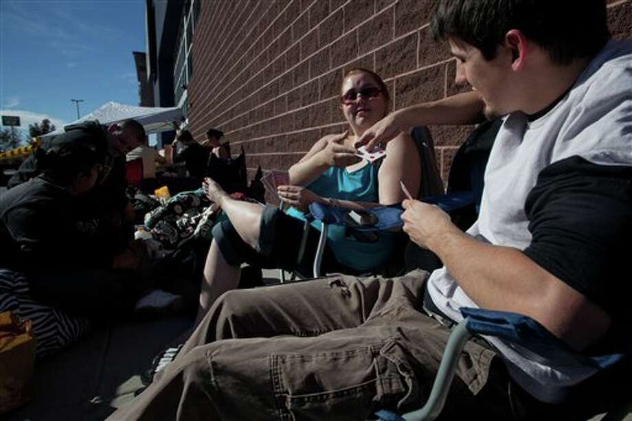Matt Faulkner, right, and Victoria Tanski play a game of go fish while they wait in line Thursday, Nov. 22, 2012 for the Black Friday sale to begin at midnight at Best Buy in St. George, Utah. Photo: Jud Burkett / The Spectrum & Daily News, AP / THE SPECTRUM & DAILY NEWS