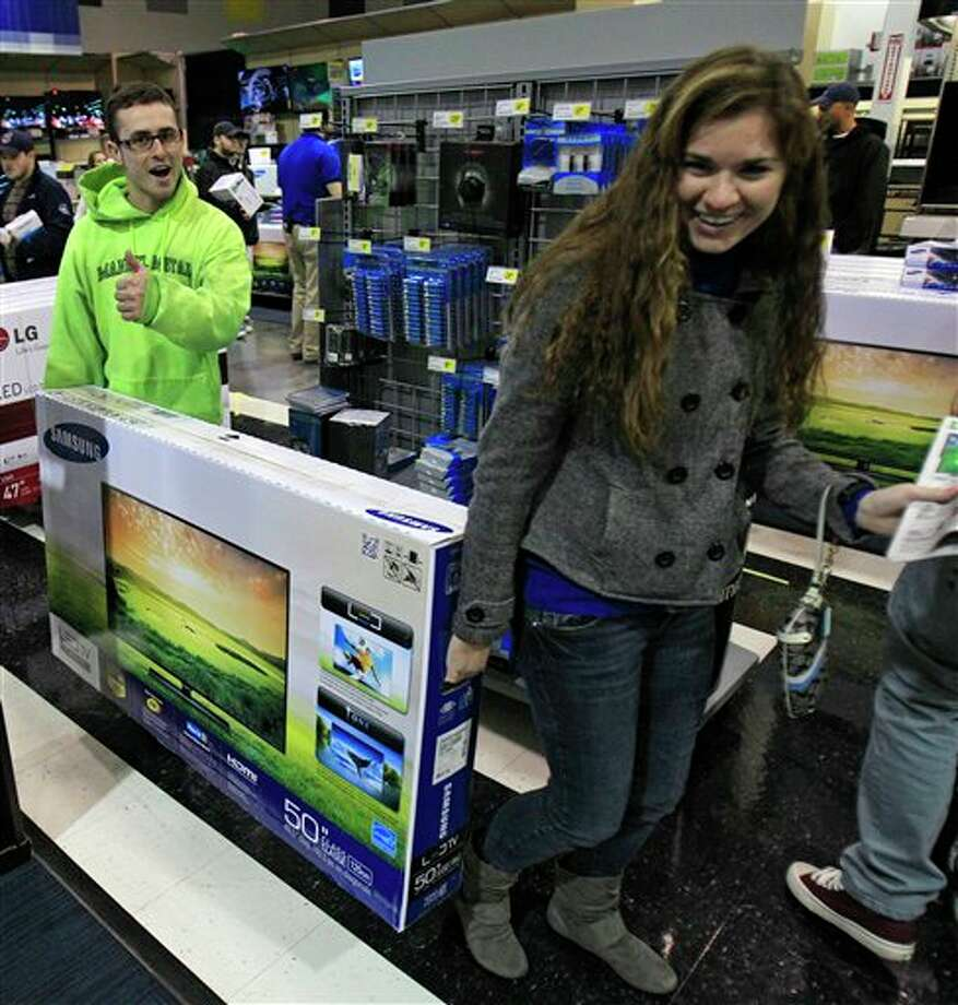 Josh Blankfeld, left to right, gives a thumbs-up as Blankfeld and Erin Burke carry a 50-inch television to the checkout at a Best Buy Friday, Nov. 23, 2012, in Mayfield Heights, Ohio. The store opened at 12 a.m. on Friday. Photo: Tony Dejak, AP / AP2012