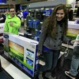 Josh Blankfeld, left to right, gives a thumbs-up as Blankfeld and Erin Burke carry a 50-inch television to the checkout at a Best Buy Friday, Nov. 23, 2012, in Mayfield Heights, Ohio. The store opened at 12 a.m. on Friday.