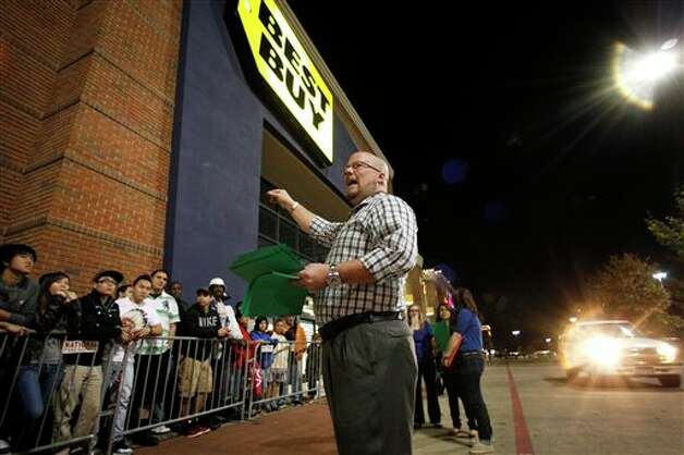 Best Buy general manager Shaun Ogdie, right, gives instructions to shoppers before handing out  sale vouchers on popular electronics items before the store opened at midnight for Black Friday sales Thursday Nov. 22, 2012, in Arlington, Texas. Photo: Tony Gutierrez, AP / AP2012
